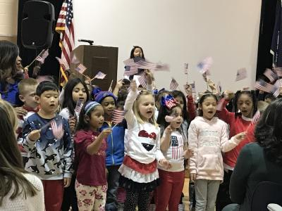 first graders singing and waving flags